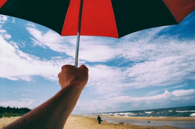 Umbrella in hand on a beach http://barnimages.com/