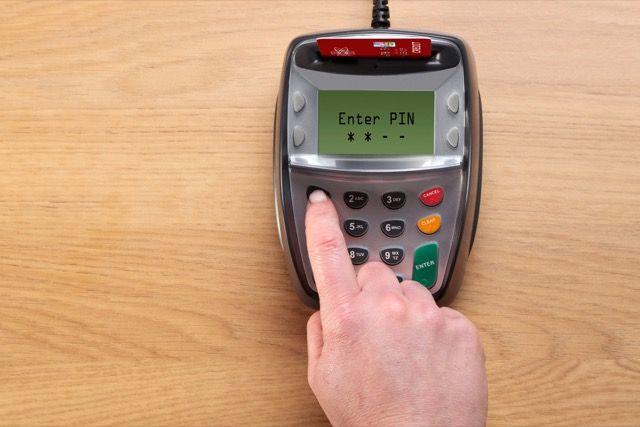 Someone entering their PIN into a card reader