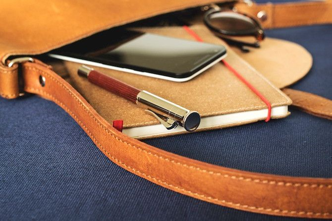 Notebook and Phone Hanging Out of a Bag