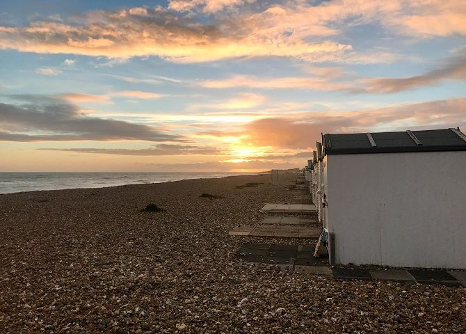 sunset on beach with sheds