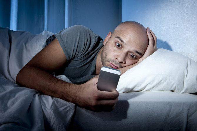 man on smartphone while in bed