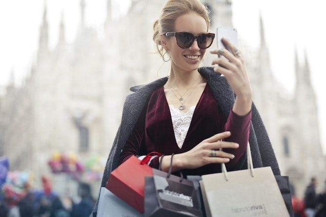 Woman with shopping bags looking at phone