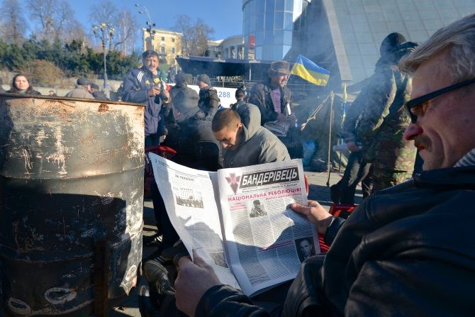 Man reads a newspaper, revealing his political viewpoint