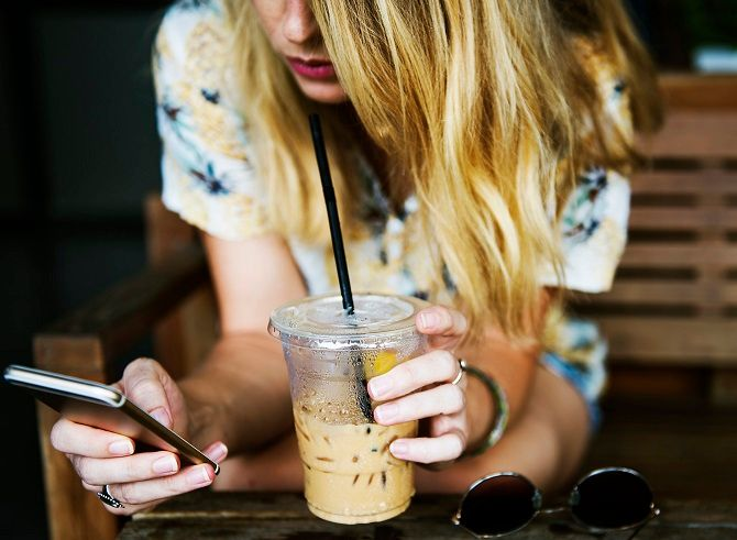 Woman drinking coffee and looking at iPhone