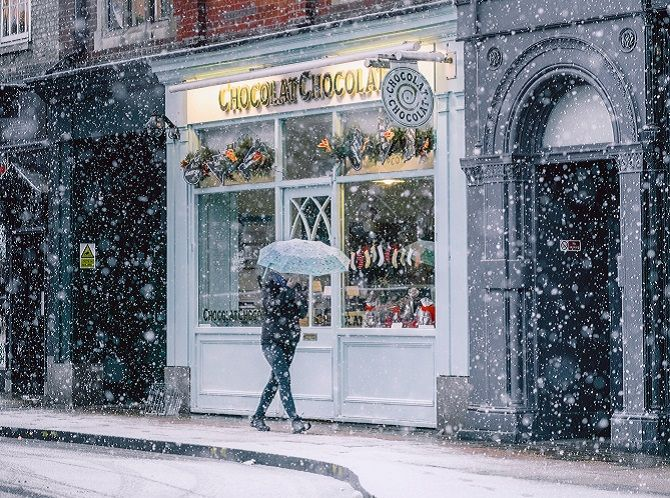 Walking past cafes and shops at Christmas while it snows