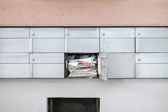 Targeted junk mail ads filling a mail box