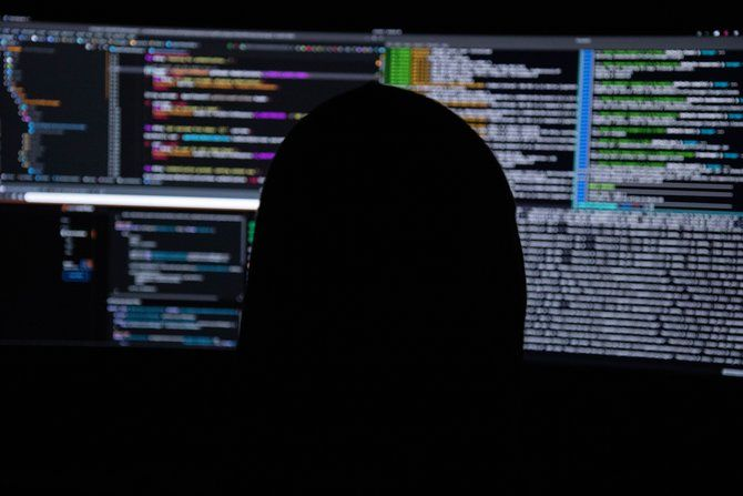 Person in shadow looking at computer monitors