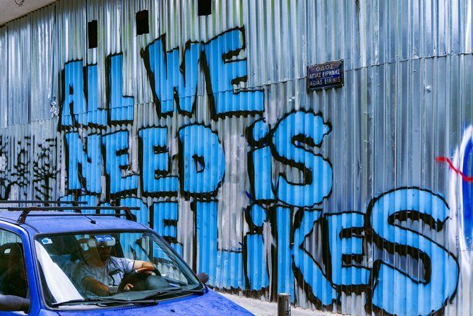 "Car beside a wall of graffiti that reads ""All We Need Is More Likes"""