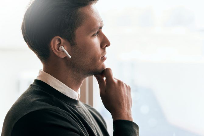 Man thinking while he looks out of window wearing wireless in ear headphones