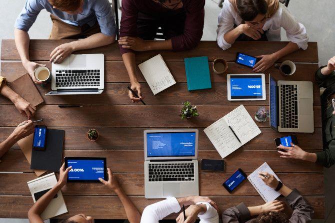 Группа сидит за столом с компьютерами