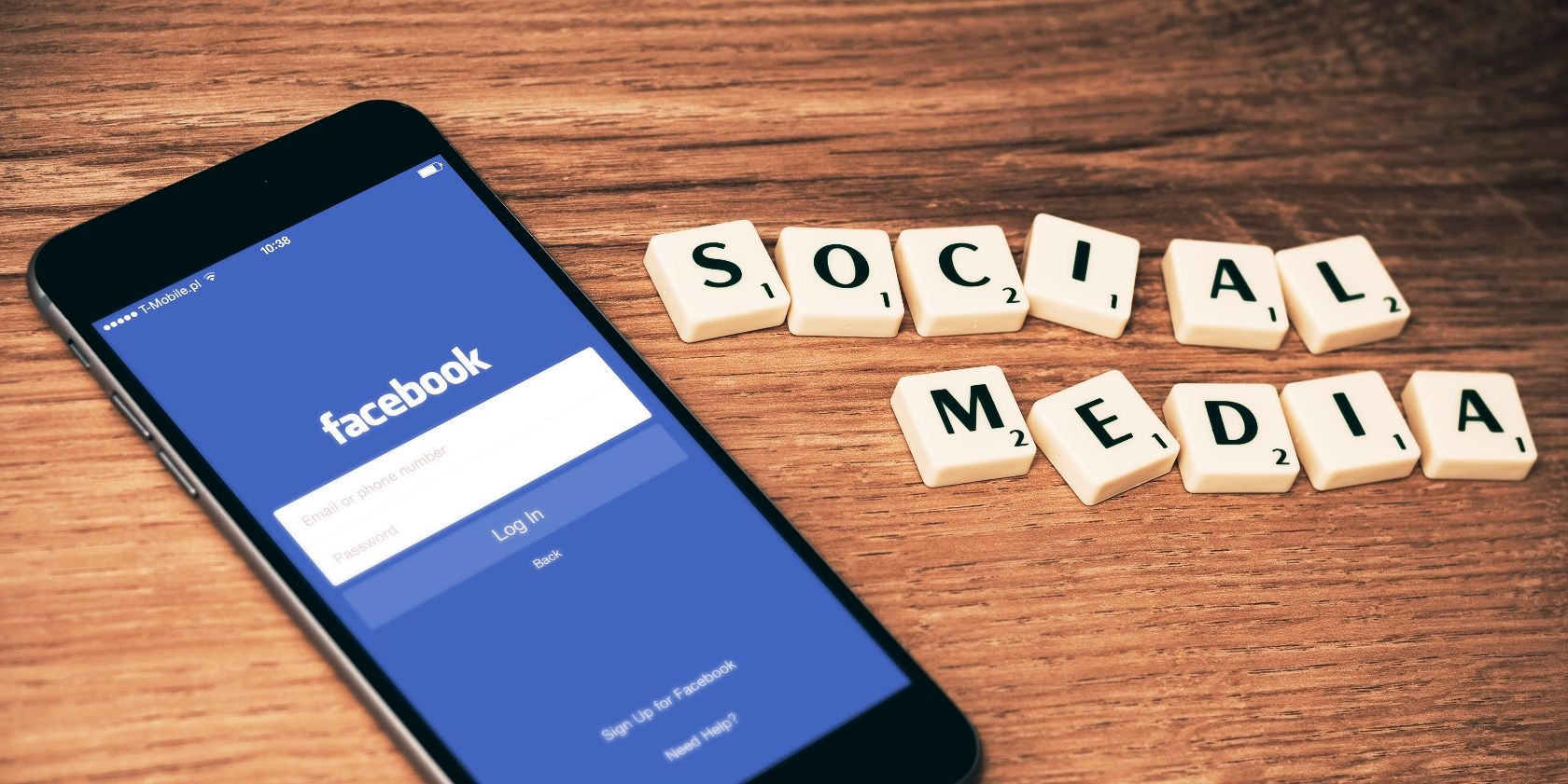 Mobile device with Facebook login screen, placed to Scrabble pieces spelling social media