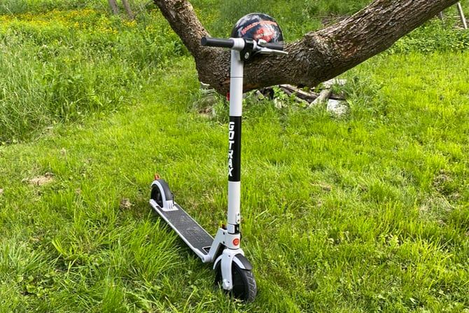 Scooter leaning against a tree